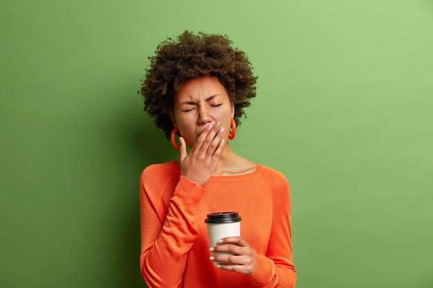Фото красивой уставшей женщины зевает и сонно держит чашку