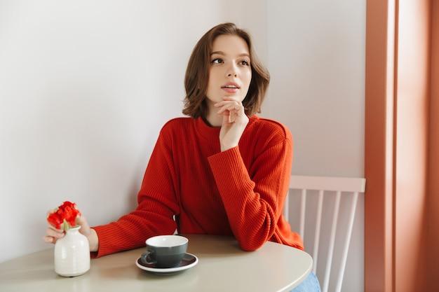 一杯のコーヒーとテーブルに座っている間、カフェで休んでいるオレンジ色のセーターの20代美女の写真