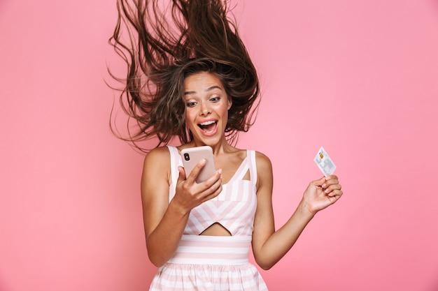 ピンクの壁に隔離された、笑顔で髪を振って携帯電話を保持しているドレスを着ている美しい女性20代の写真