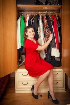 大きなワードローブに座っている赤いドレスを着た美しい女性の写真