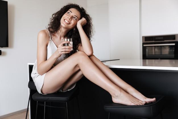 居間の椅子に座って、水のガラスを保持しながら、脇を見て家庭服を着ている美しい女性の写真