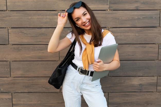 Фотография красивой женщины, носящей белую футболку, держащую компьютерный ноутбук и черные солнцезащитные очки, оставаясь на улице и смотрящую в камеру.