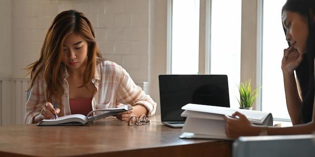 Фото красивых женщин читая книгу и ослабляя совместно пока сидящ на деревянном столе над удобной гостиной. женщины с расслабляющей концепцией времени.