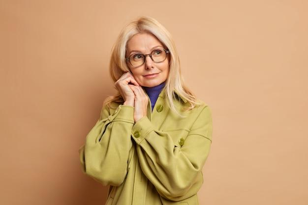 美しいしわの寄った50歳の女性の写真は、顔の近くに手を置き、ファッショナブルなコートを着てしんみりと脇を向いています。
