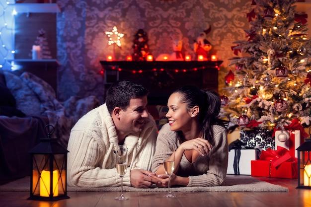 クリスマスを祝う冬の自宅で美しい若いカップルの写真。クリスマスのお祝いでロマンチックな雰囲気。
