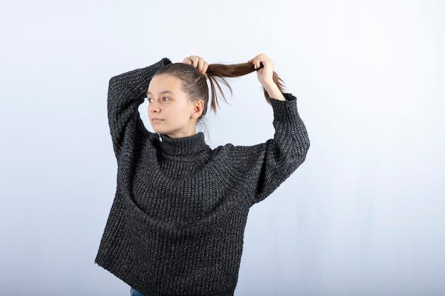 회색에 그녀의 머리를 고정하는 아름 다운 젊은 여자의 사진.