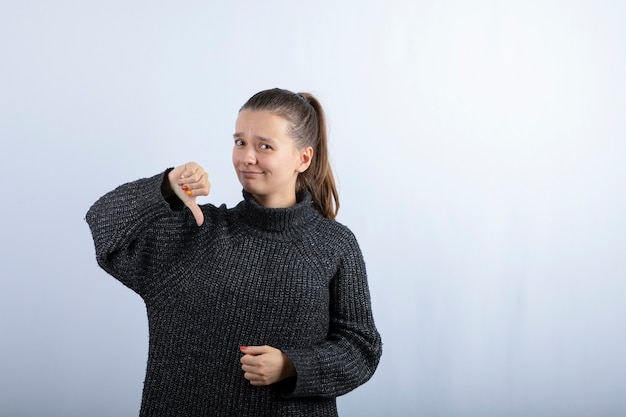 灰色に親指を下に与える美しい少女の写真。