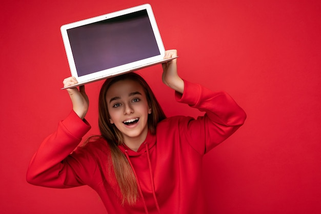 Фото красивой молодой девушки, держащей компьтер-книжку компьютера смотря камеру изолированную над красочным фоном.
