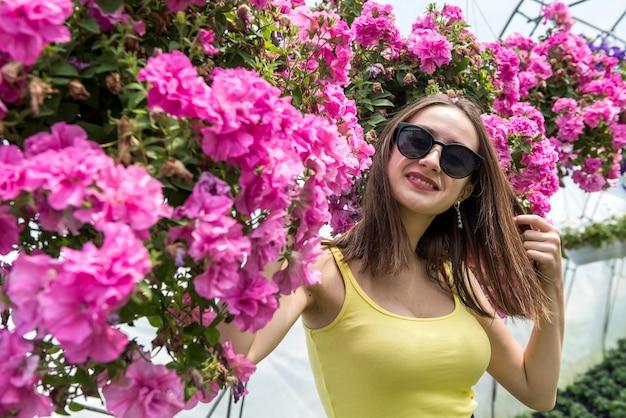 温室で花の間でポーズをとって美しい少女の写真。ライフスタイル
