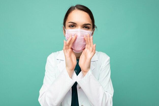 白衣と青の上に孤立して立っている医療マスクの美しい若い女性医師の写真