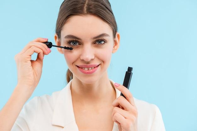 Фото красивой молодой женщины, позирующей изолированной, удерживая тушь для ресниц, делая макияж.