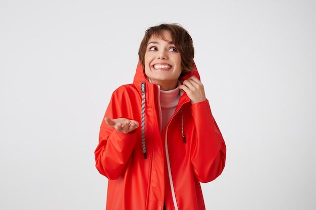 赤いレインコートを着て、左を見上げて、フードに隠れて、手のひらを雨の下に置く、美しさの若い笑顔の短い髪の女性の写真。立っている。