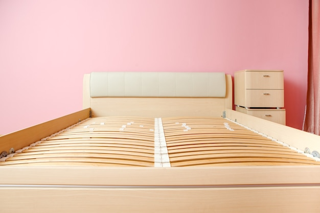 マットレスなしのベッド、部屋の引き出しのチェストの写真