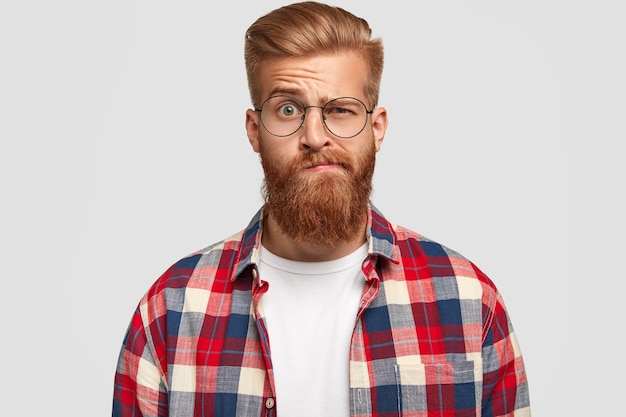 Фотография сбитого с толку озадаченного мужчины с густой рыжей бородой и усами, поднимающего брови, сомневающегося, одетого в модную одежду, изолированного на белой стене. выражения лица