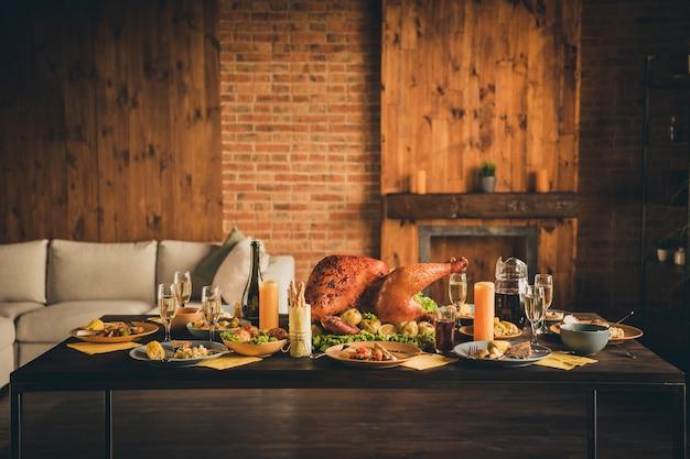 Фотография большого запеченного жаркого, фаршированного салатом из индейки, фруктовый декор, канадская семья, оставила тарелки для украшения, бутылка игристого вина, желтая салфетка, две свечи в гостиной, без людей в помещении
