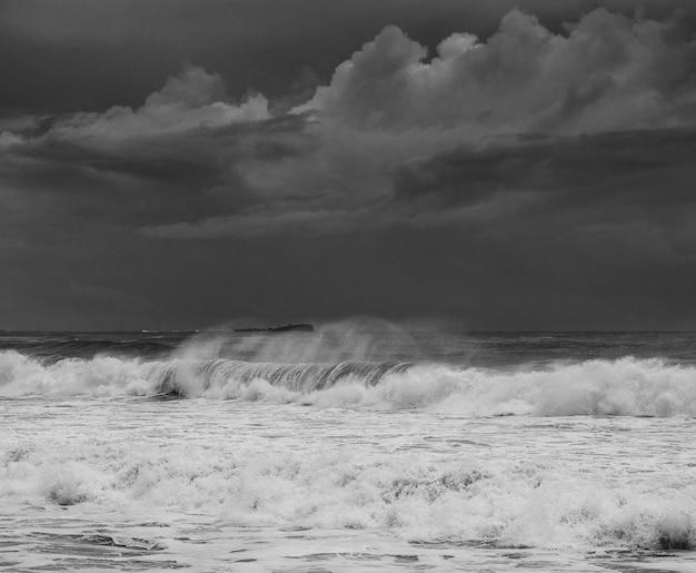 Фотография больших волн на солнечном побережье под темным облачным небом в квинсленде, австралия.