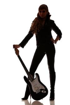 가죽 레깅스와 부츠에 여성 다리 옆에 흑백 기타의 사진. 흰색 배경에 고립