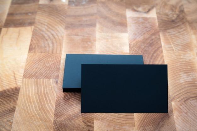 木製の背景に黒の空白の名刺の写真。