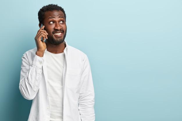 黒人の流行に敏感な男の写真は、電話で会話し、携帯電話を耳の近くに持ち、友人にニュースを伝え、集中し、白いシャツを着ています。成功した実業家は携帯電話を介して予定を立てます