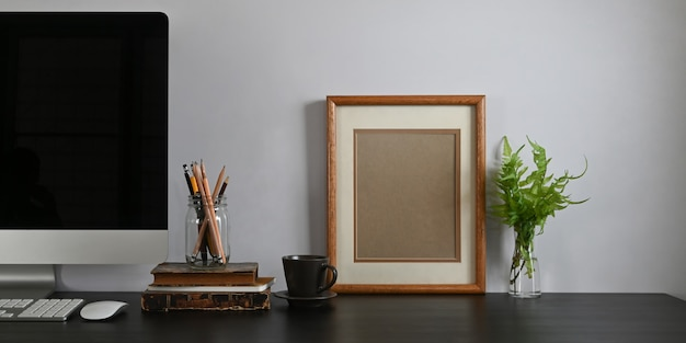 검은 빈 화면 컴퓨터 모니터, 책, 노트북, 연필 홀더, 액자, 화분 흰색 시멘트 벽에 함께 넣어 함께 검은 책상의 사진.