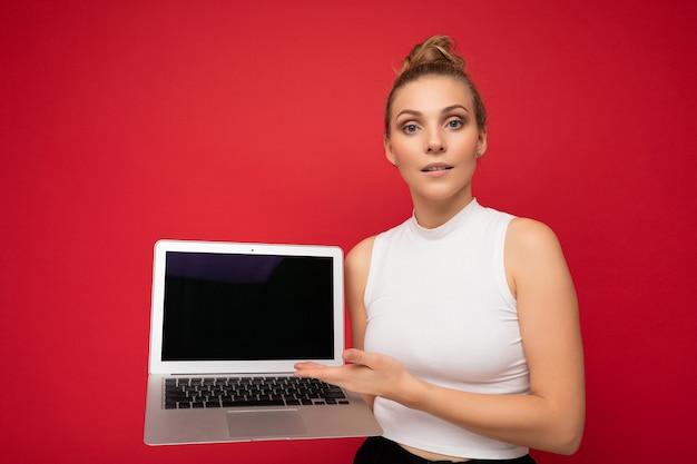 컴퓨터 노트북을 들고 카메라를보고 모여 머리를 가진 금발의 젊은 여자의 사진