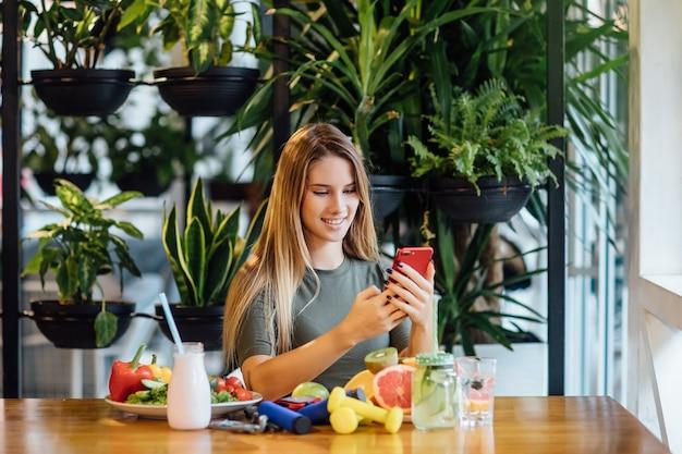 金髪のフィテストレーナーの写真は、手に電話と健康的な食べ物を持ってテーブルに座っています