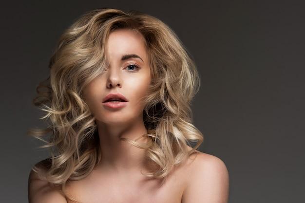 裸の肩を持つ巻き毛のブロンドの写真