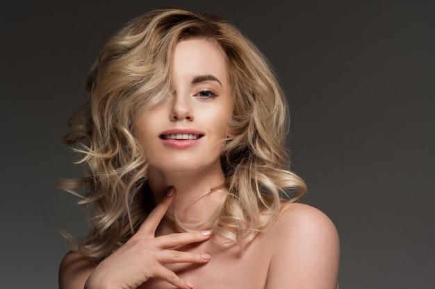 裸の肩を持つ巻き毛のブロンドの女性の写真