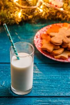 생강 비스킷, 우유 한 잔, 화환을 태우는 가문비 나무 가지가있는 파란색 테이블 사진