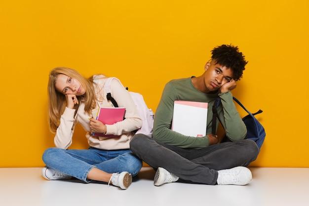 黄色の背景の上に分離された、足を組んで床に座って練習帳を持って使用している退屈または動揺している学生の写真