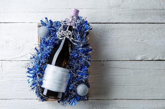 반짝이, 흰색 테이블에 크리스마스 공 상자에 빈 카드와 함께 와인 한 병의 사진