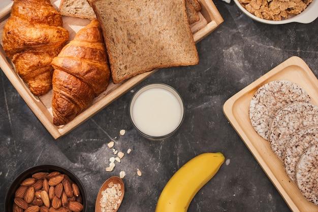 Фотография хлеба, булочки, молока, миндаля и свежего молока на столе. приготовление завтрака, ежедневный продукт.