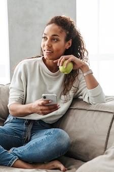 明るいアパートのソファに座っている間、携帯電話を使用してブルネットのアフリカ系アメリカ人女性の写真