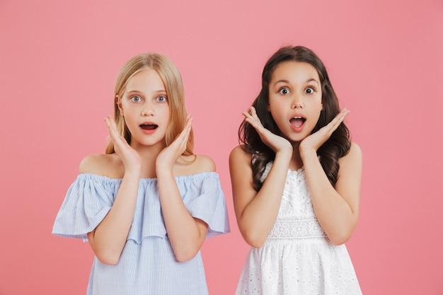 驚きや喜びを表現するドレスを着て、口を開けて顔に手を上げるブルネットとブロンドの王女の女の子の写真。