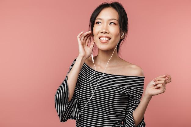 기본적인 옷을 입고 노래를 부르고 빨간 벽에 격리된 이어폰으로 음악을 듣는 갈색 머리 아시아 여성의 사진