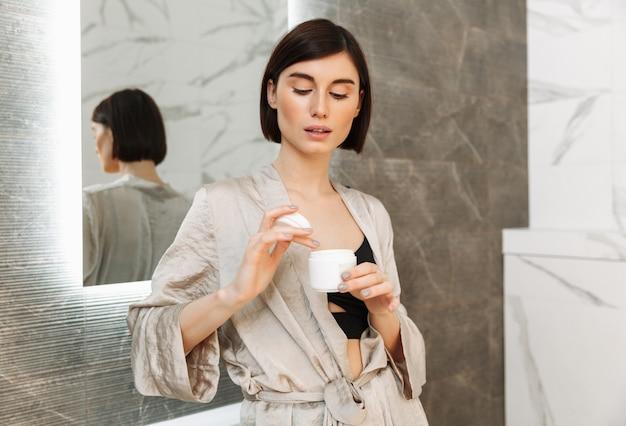 鏡の近くに立って、家のバスルームでフェイスクリームと銀行を保持しているブルネットの美しい女性の写真
