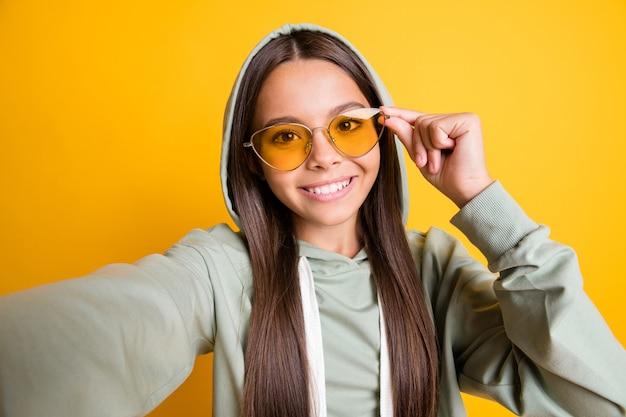 黄色の背景に分離されたオンラインブログアームタッチサングラスの写真を作るブルネットの髪の小さな人の写真