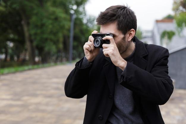 야외 산책하는 동안 레트로 카메라에 촬영 검은 코트를 입고 갈색 머리 남자 20 대의 사진