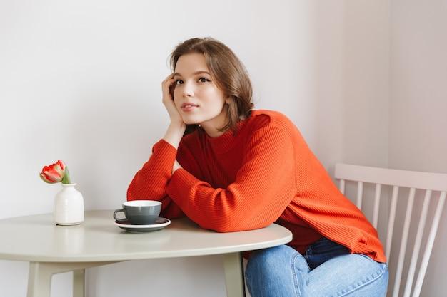 テーブルに座ってレストランで休んでいるオレンジ色のセーターの20代ブルネットの女性の写真