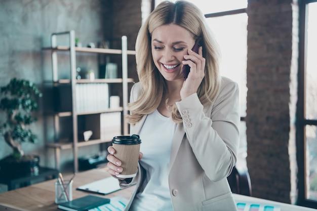 전화 컵 이야기를 들고 비즈니스 레이디의 사진