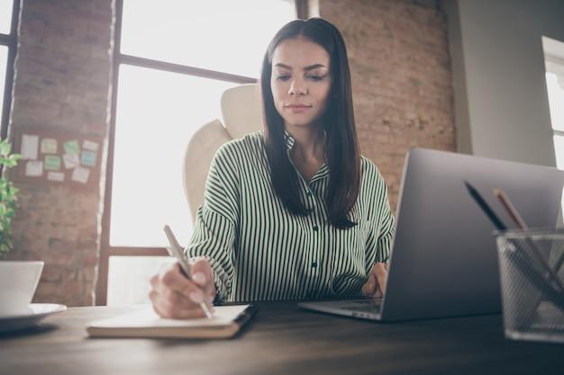 Фотография бизнес-леди делает заметки в тетради в офисе
