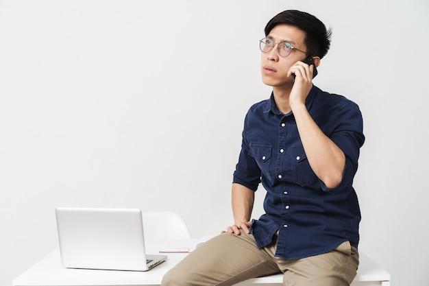 흰색 벽에 격리된 사무실에서 노트북으로 작업하는 동안 안경을 쓰고 테이블에 앉아 스마트폰으로 이야기하는 사업가 같은 아시아 남성의 사진
