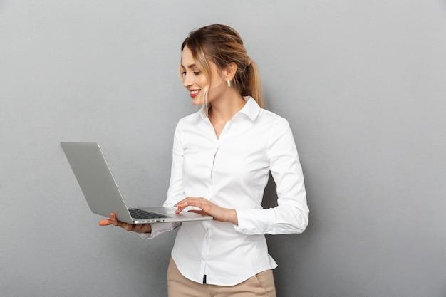 分離された、オフィスで立ってラップトップを保持しているフォーマルな服装のビジネスライクな女性の写真