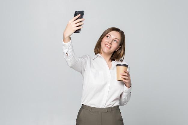 Фотография деловой женщины в официальной одежде, держащей в руке кофе на вынос и делающей селфи на мобильном телефоне над серой стеной