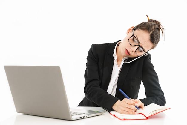 机に座って白い壁に隔離されたオフィスでラップトップに取り組んでいるフォーマルな服を着た忙しい女性労働者の実業家の写真