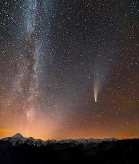 Фотография кометы c / 2020 f3 (neowise). ночной пейзаж гор со звездами покрыл млечный путь.