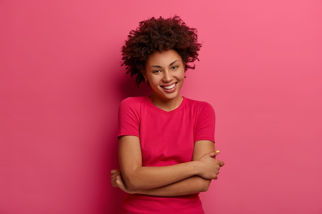 自然な巻き毛ののんきな女性の写真、手を体に交差させて、心地よく微笑んで、カジュアルな話をして、tシャツを着て、良い一日を楽しんで、バラ色の壁に隔離されています。幸せな気持ち