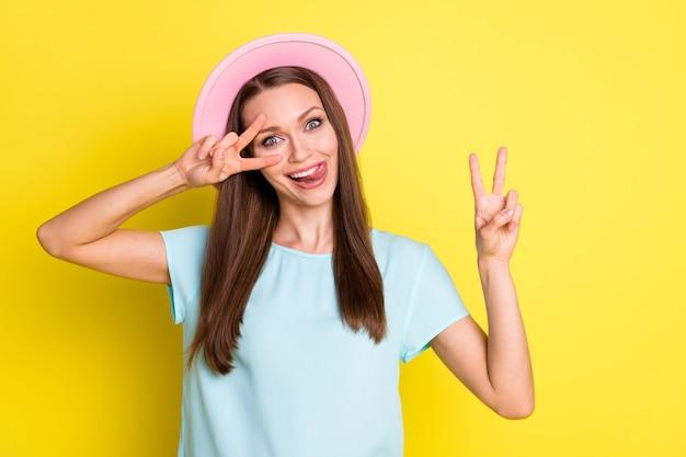 부주의한 장난꾸러기 소녀의 사진은 자유 시간을 갖고 v자 모양으로 혀 입술을 핥는 이빨을 밝은 빛나는 색 배경 위에 격리된 파란색 분홍색 모자 옷을 입는다