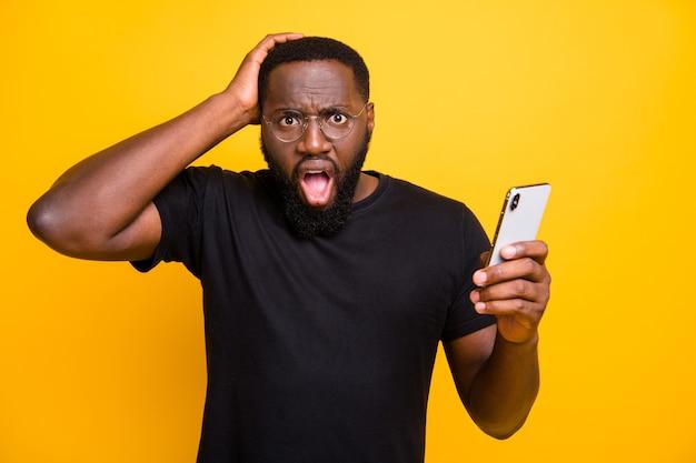 Tシャツの孤立した黄色の鮮やかな色の壁で電話を閲覧しながら偽のニュースが広がるのを見た後、彼の頭をつかんでいるカジュアルな男性の写真