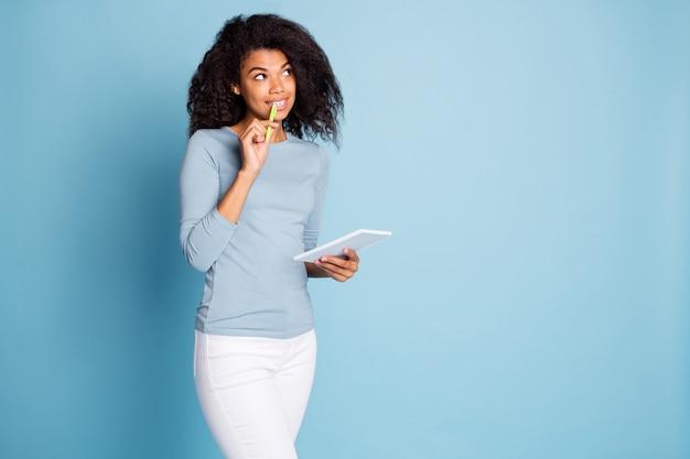 Фотография случайной удивленной сбитой с толку девушки, придумывающей новый стих, развивающей свои таланты писателя стихов в белых штанах, изолированном пастельно-синем фоне